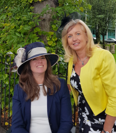 Lady in hat with navy jacket and lady with black and white dress and yellow jacket.