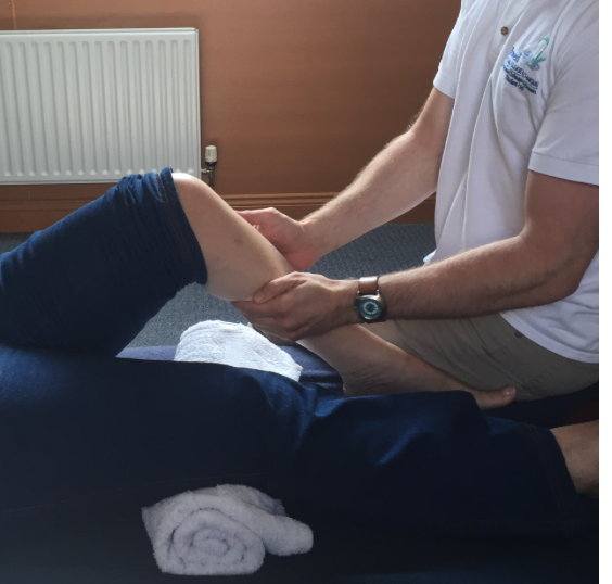 The Bowen practitioner has both hands on someone's calf