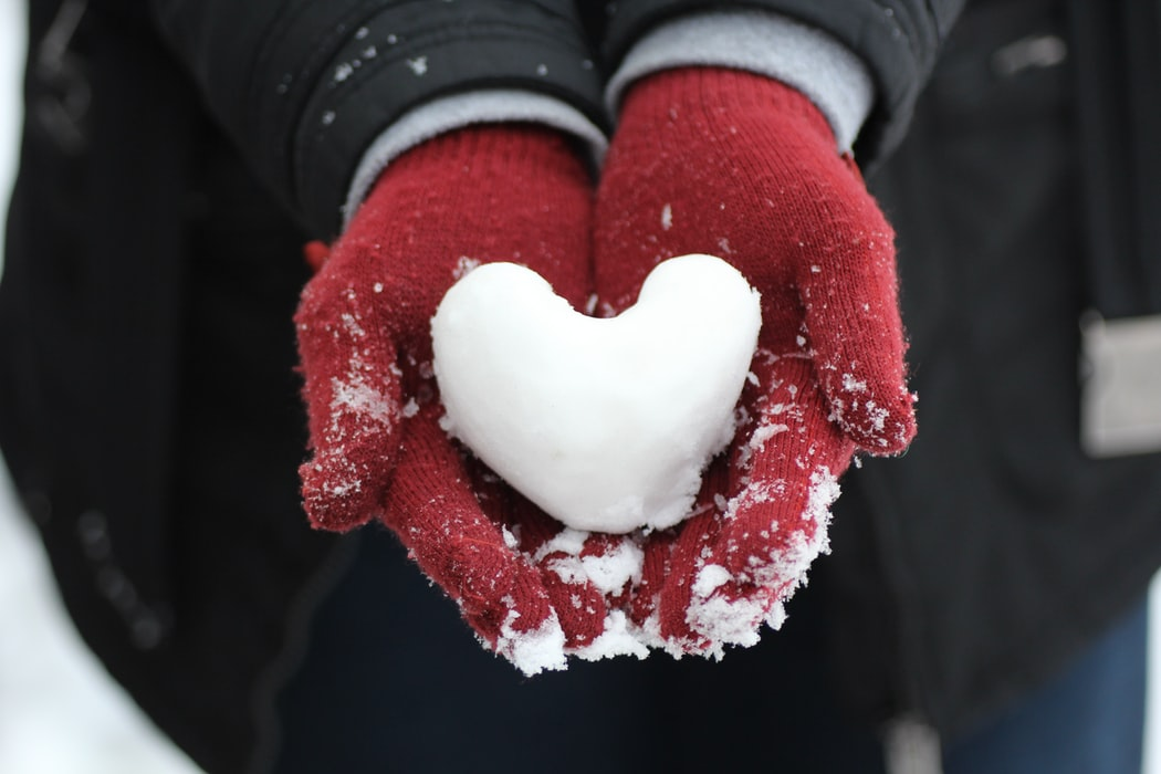 A heart shaped snowball held by a person wearing red woollen gloves